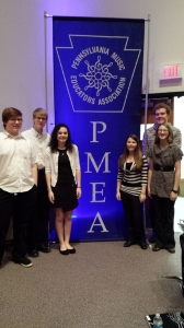 District Chorus participants pose in front of the PMEA banner. (Photo contributed by Kayla Sibeto)