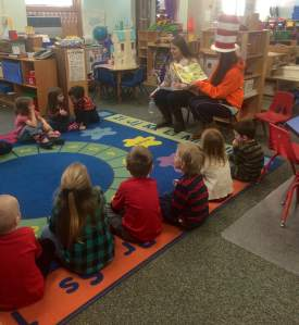 Juniors Haley Wise (left) and Maile Chang (right) read to a Head-Start class in the elementary school.